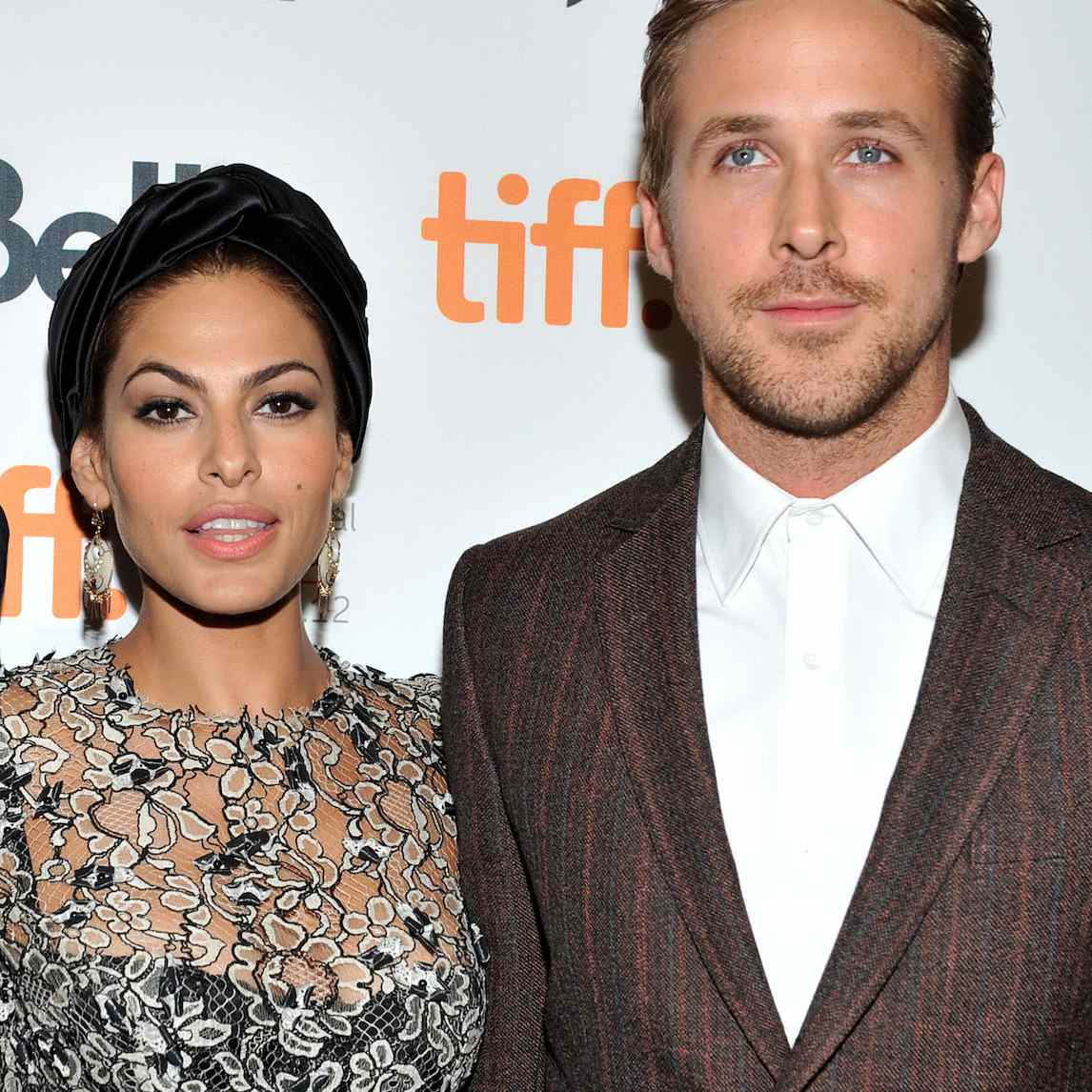 Eva Mendes stares straight into the camera in a floral lace sheer top over a black bustier next to Ryan Gosling in a brown suit