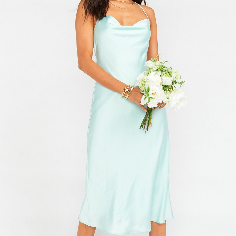 Model in a mid-length light blue satin slip gown with a cowl neck