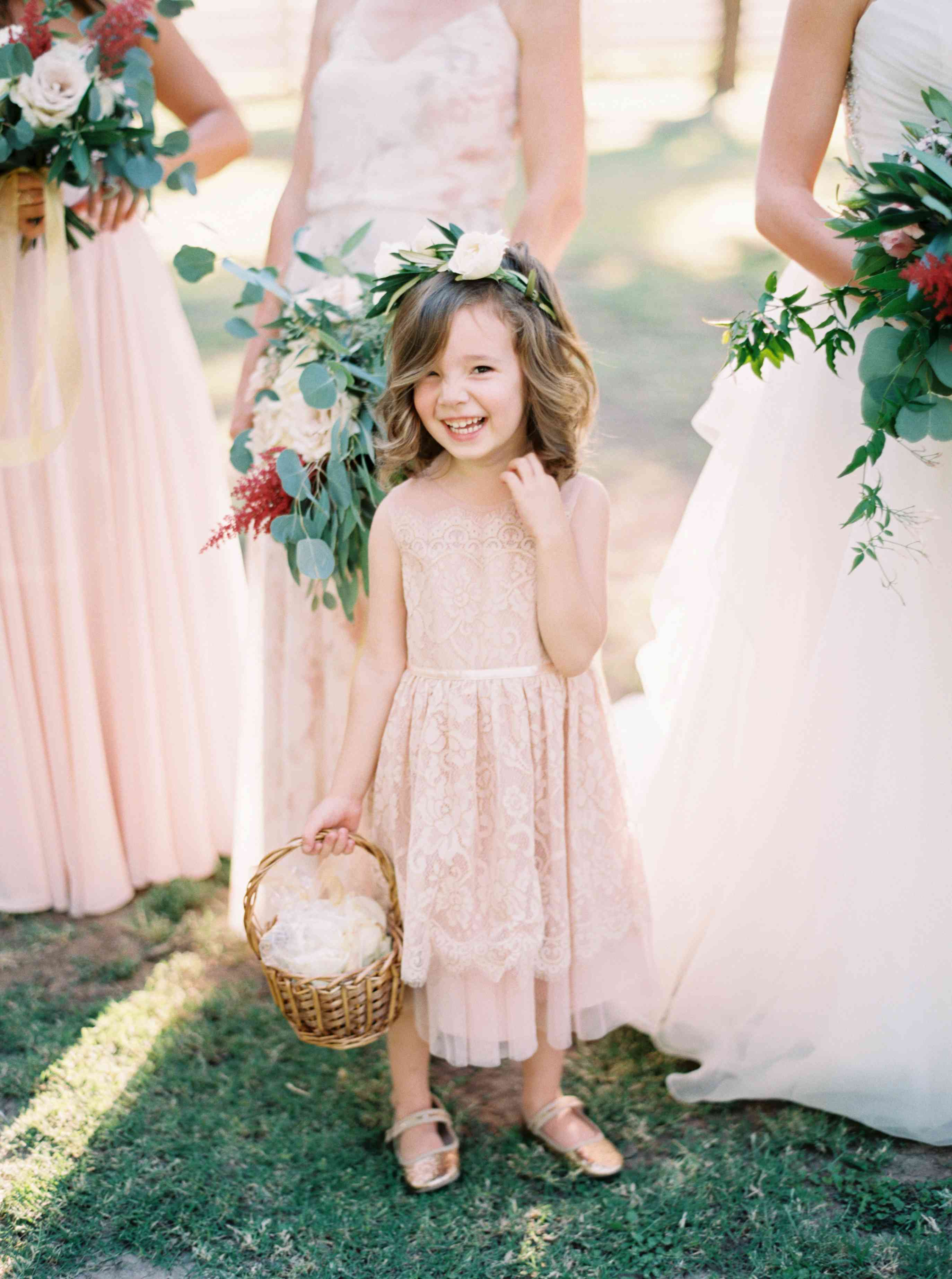 Flower girl in a pink dress with bridesmaids in pink dresses in the background