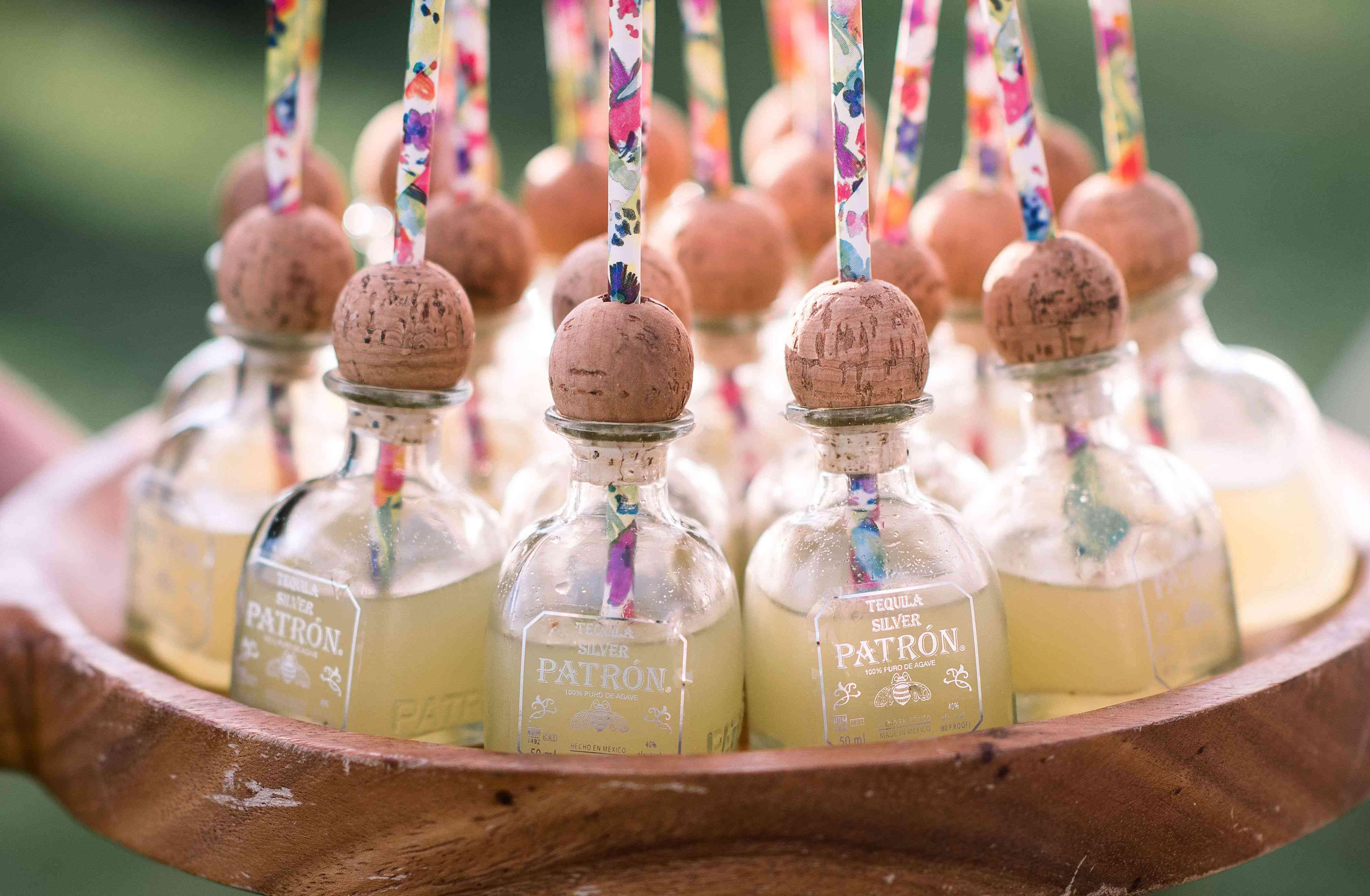 Tray of margaritas in mini Patron bottles with straws