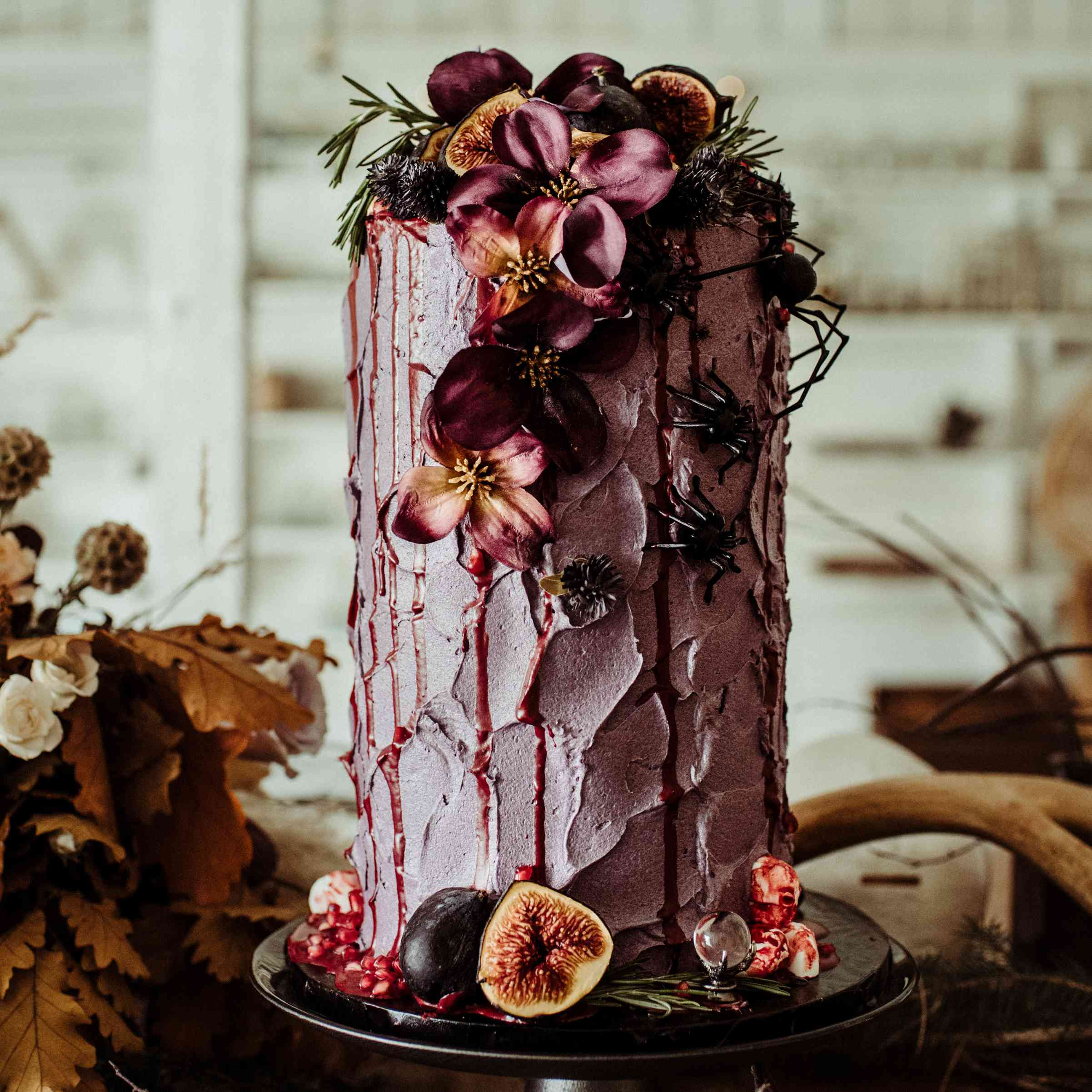Elongated dark purple wedding cake with floral and fig accents