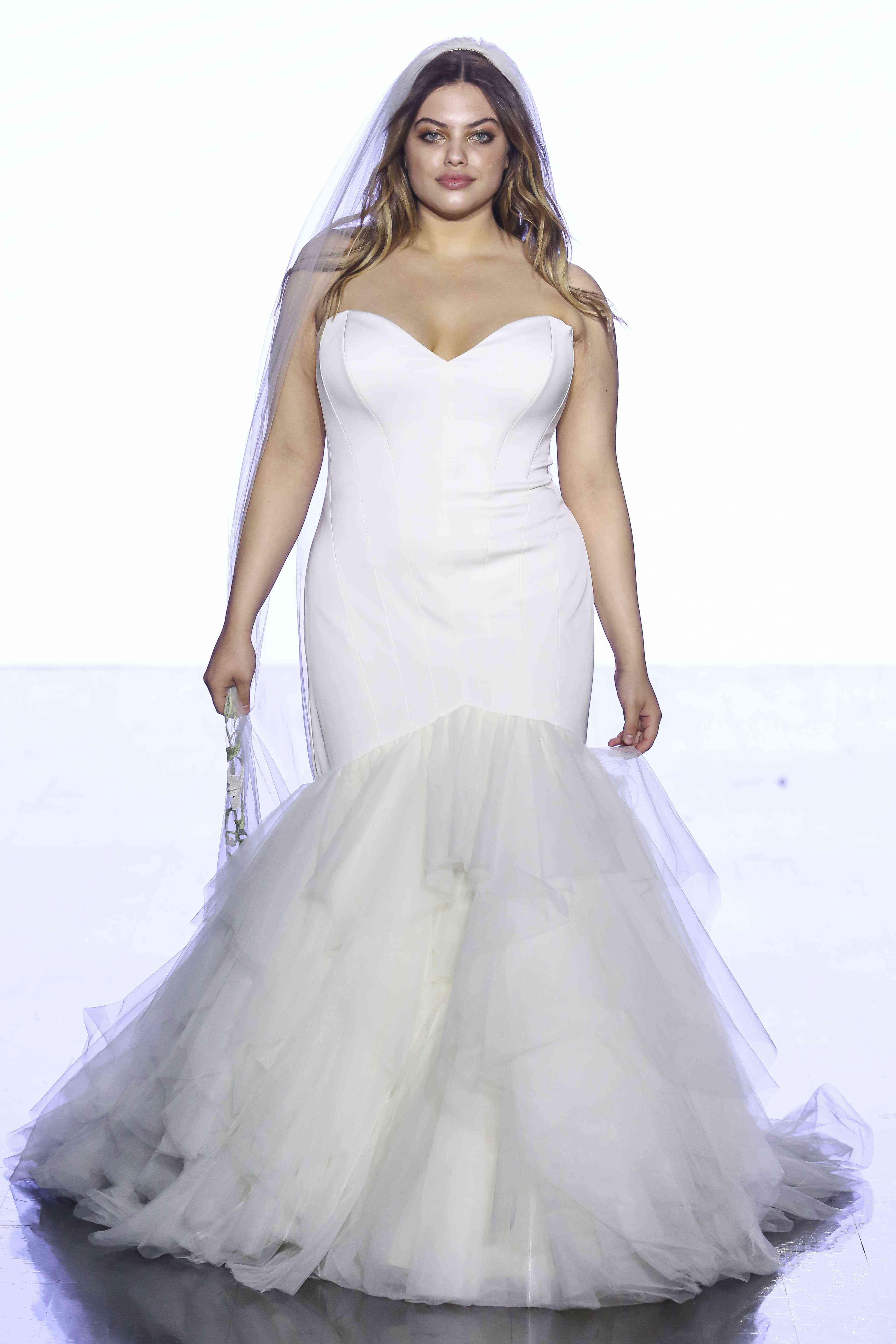 Model in strapless sweetheart satin mermaid gown with a layered tulle skirt