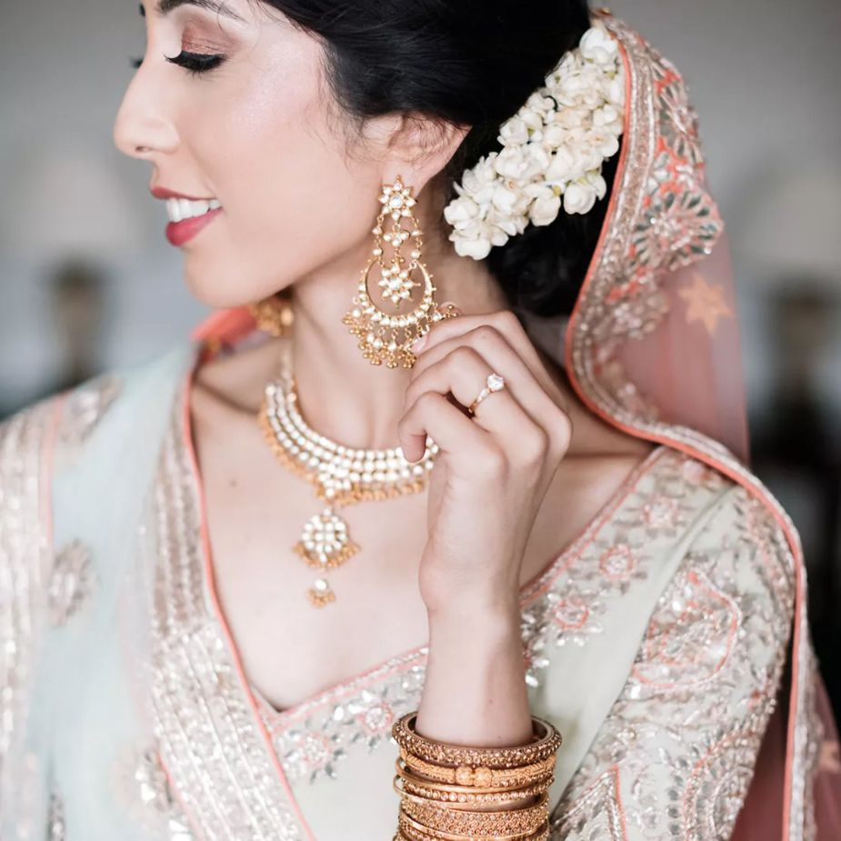 Bride with statement jewelry and flowers in chignon