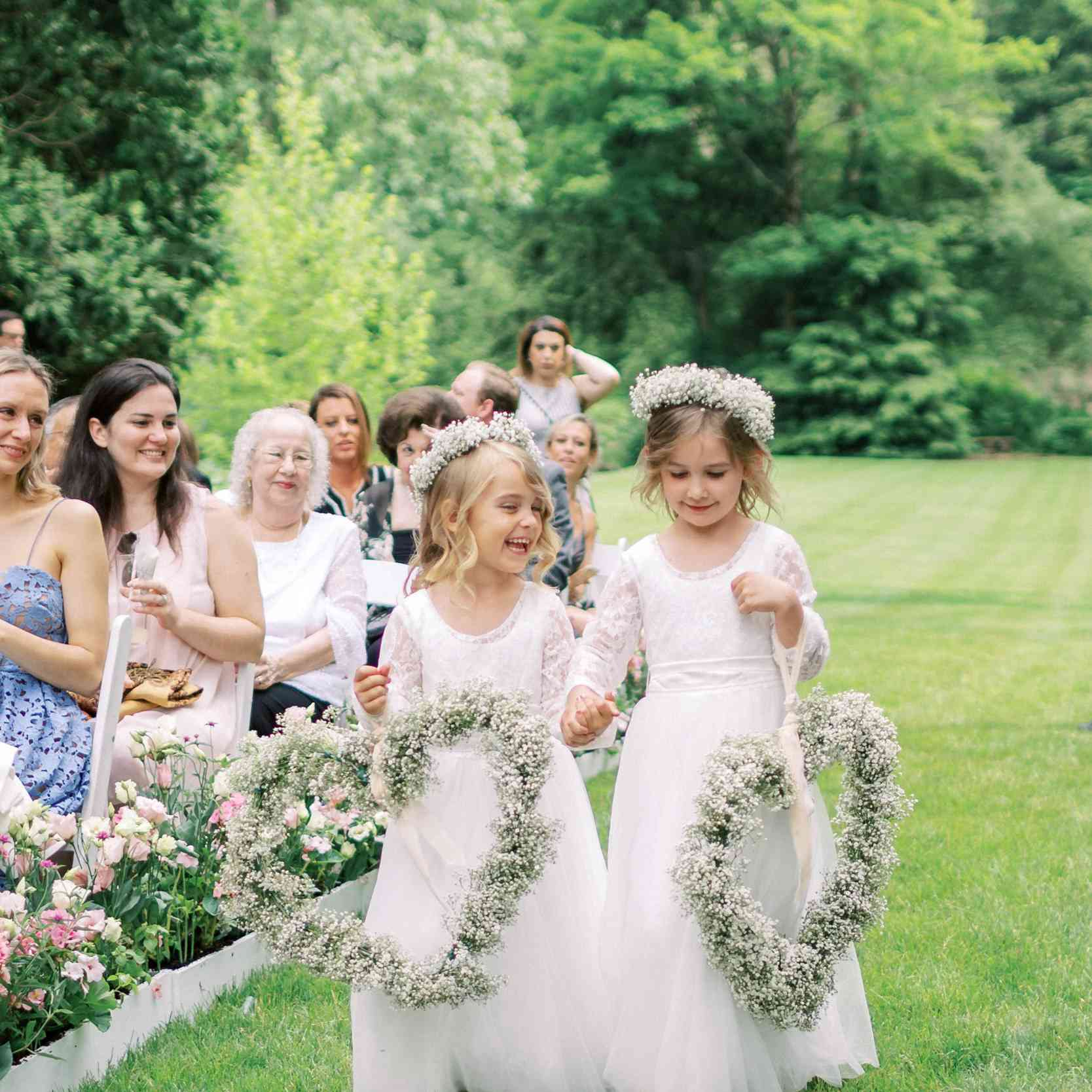 Two flower girls carrying baby's breath heart wreaths down the aisle with matching flower crowns