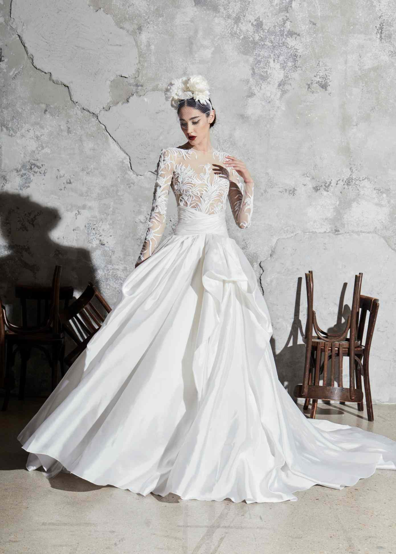 Model in a ballgown with a long-sleeve embroidered illusion bodice, a draped waistband, and a gathered silk skirt