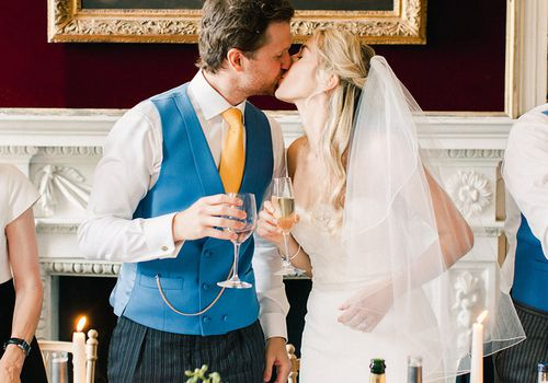 Newlyweds kissing after champagne toast