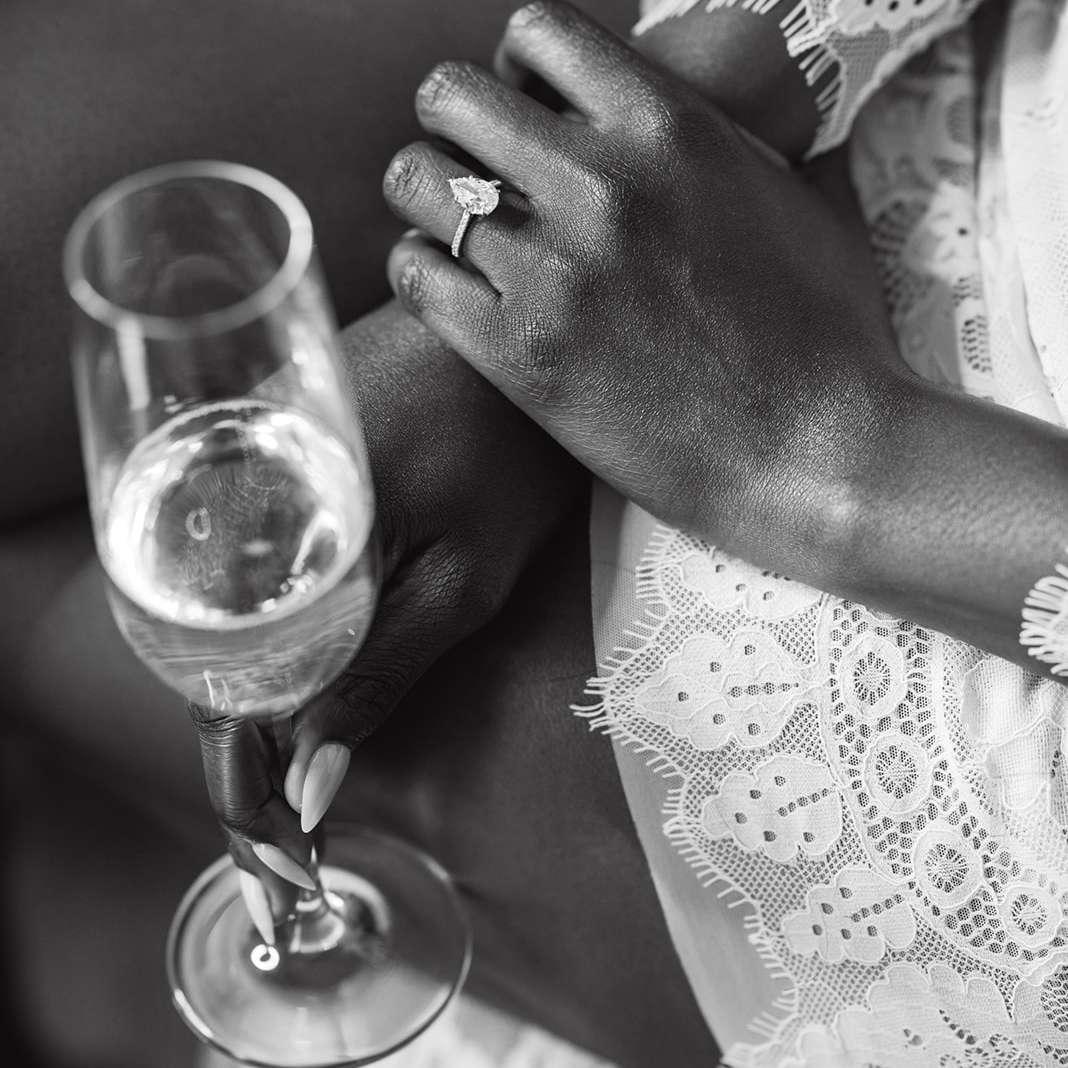 Bride's hand wearing pear-cut engagement ring holding a glass of champagne