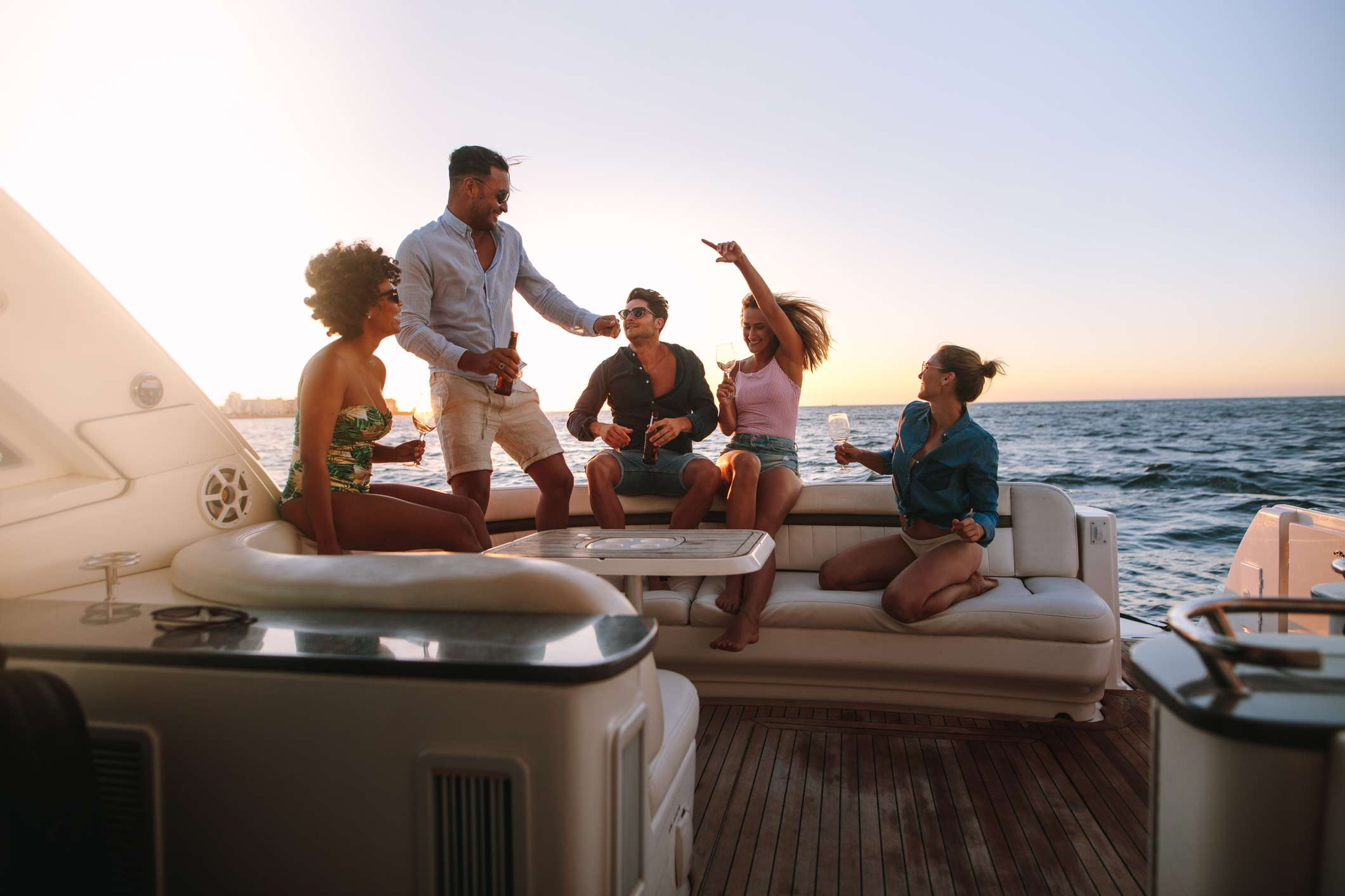 Five friends drinking beer and wine on a boat