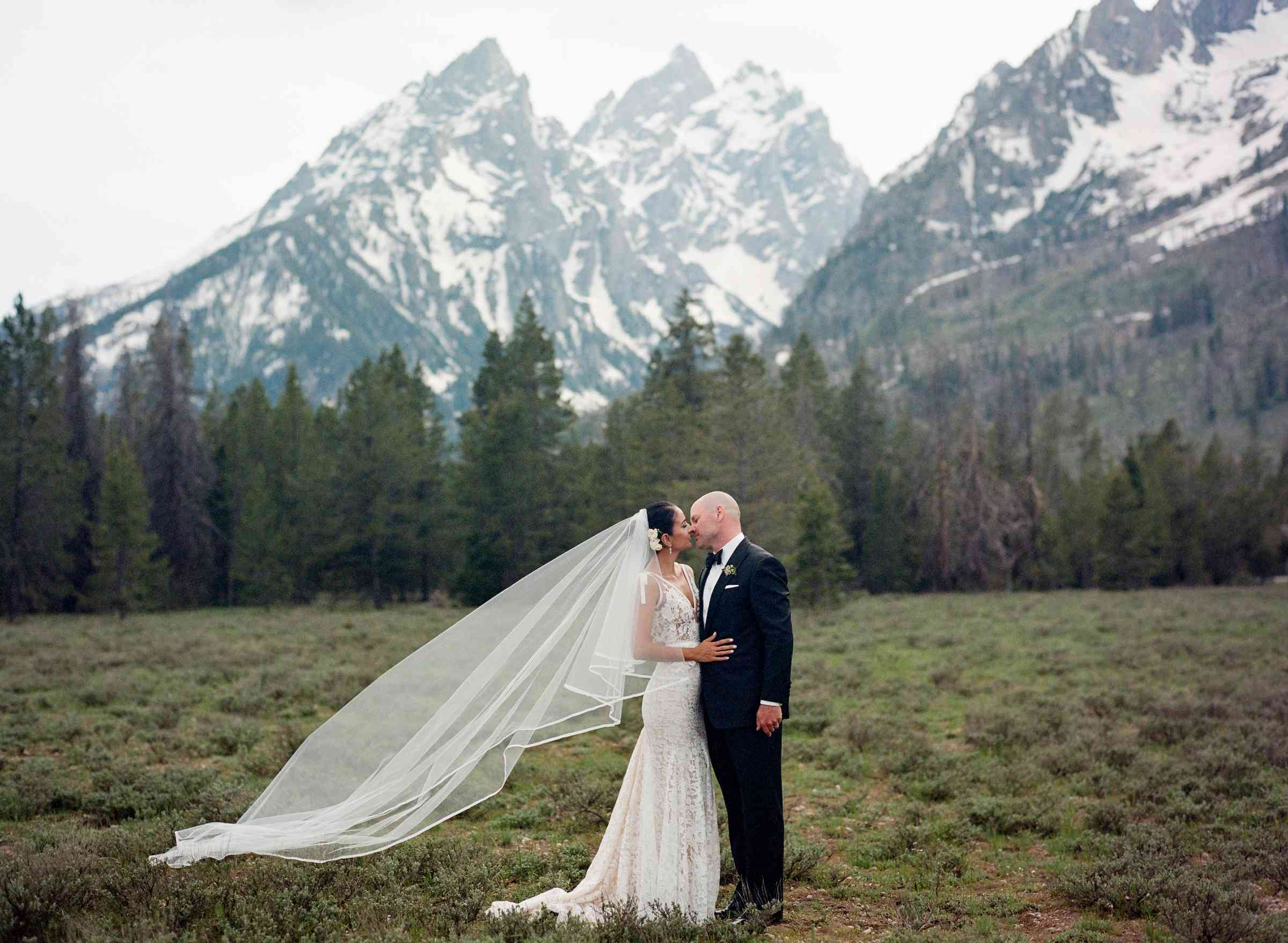 Couple kissing with mountains behind them