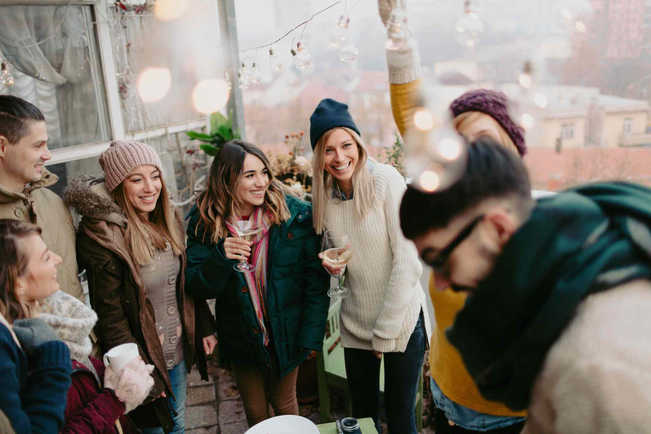 Group of friends with beverages in winter clothes at an outdoor party
