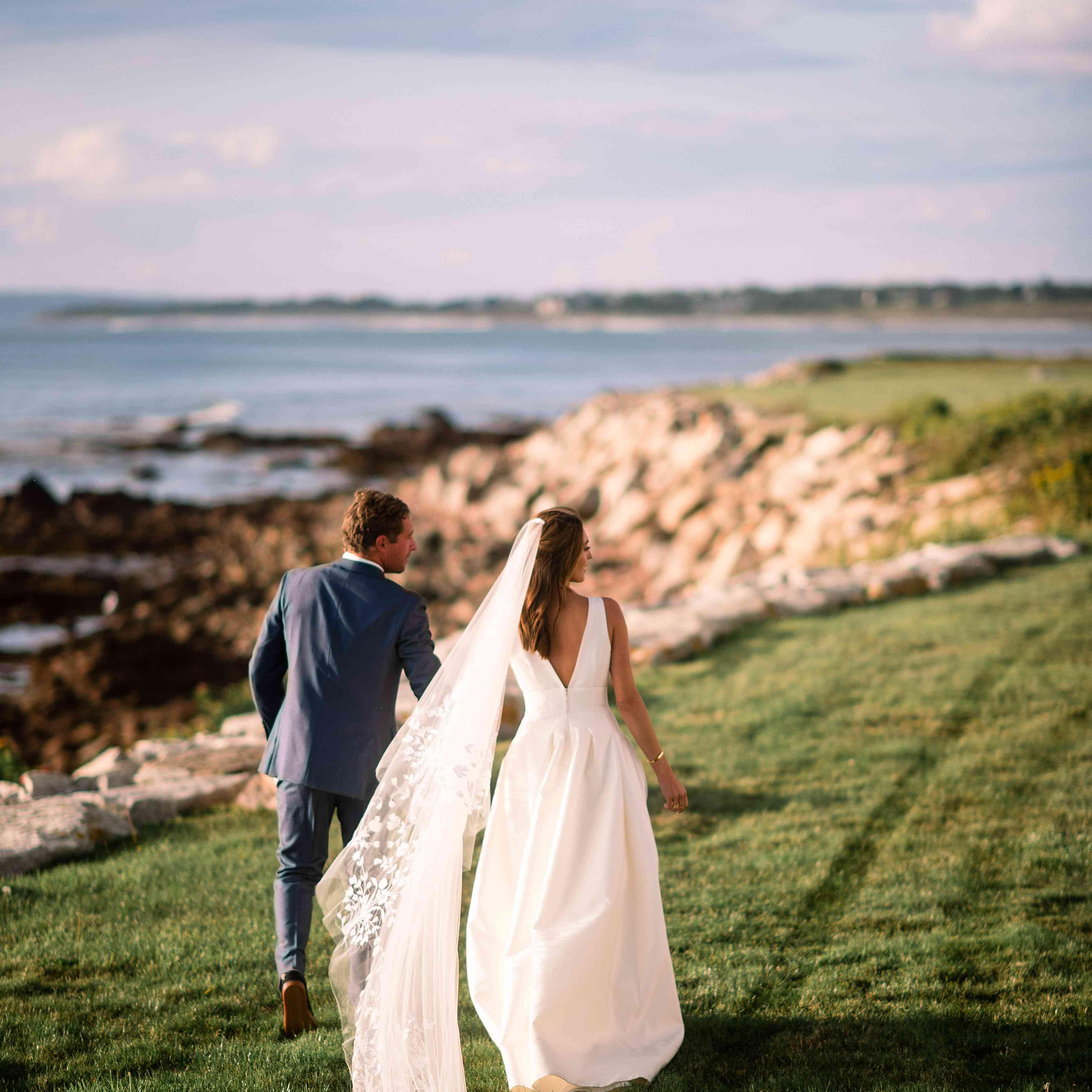 Bride and groom walking by sea