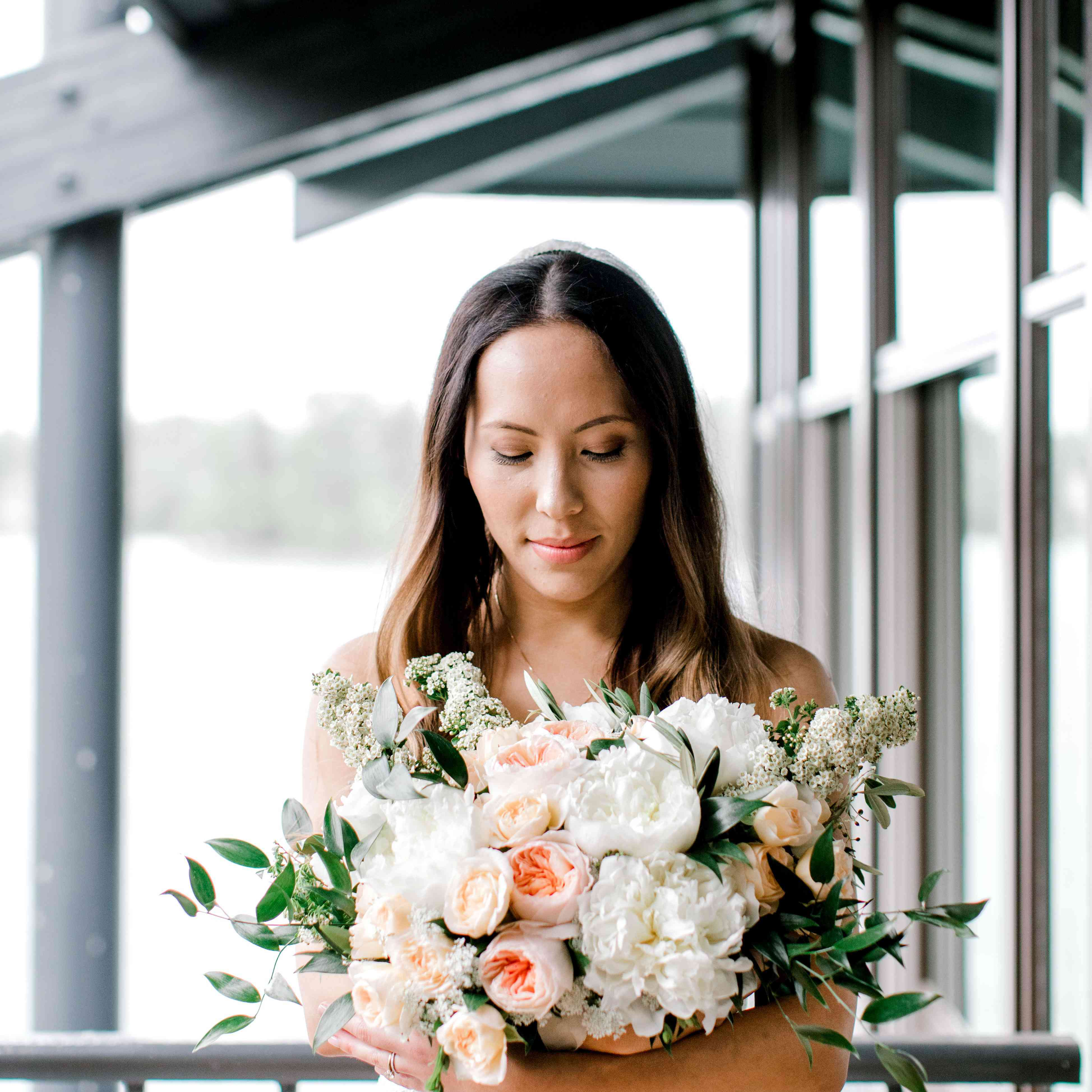 Bride holding a white and peach peony bouquet with baby's breath