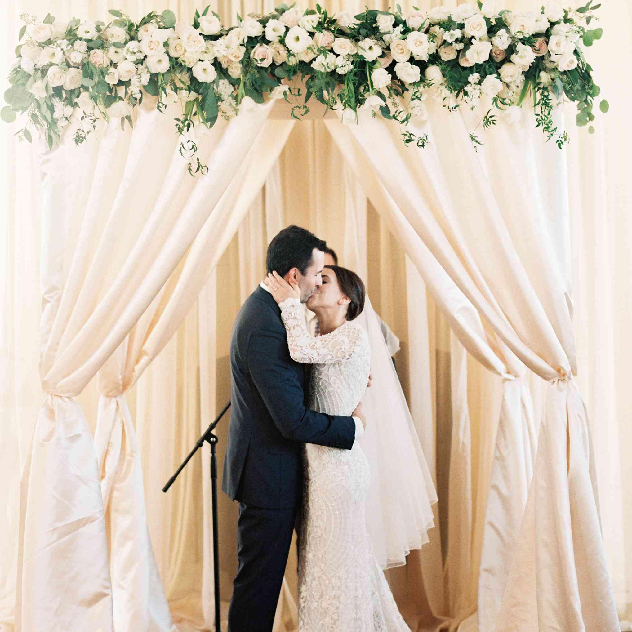 Bride and groom kiss under chuppah