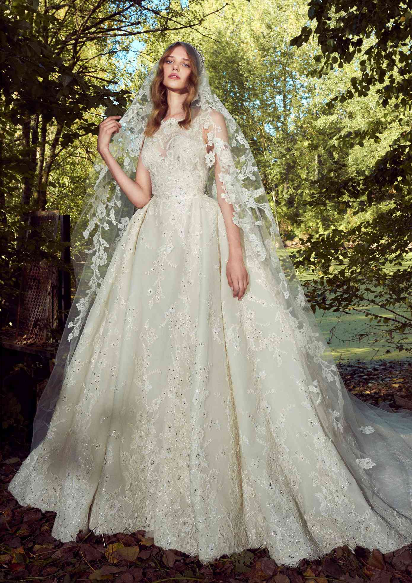 Model in an off-white high-neck sleeveless ballgown with allover sequined floral lace embroidery with a matching veil