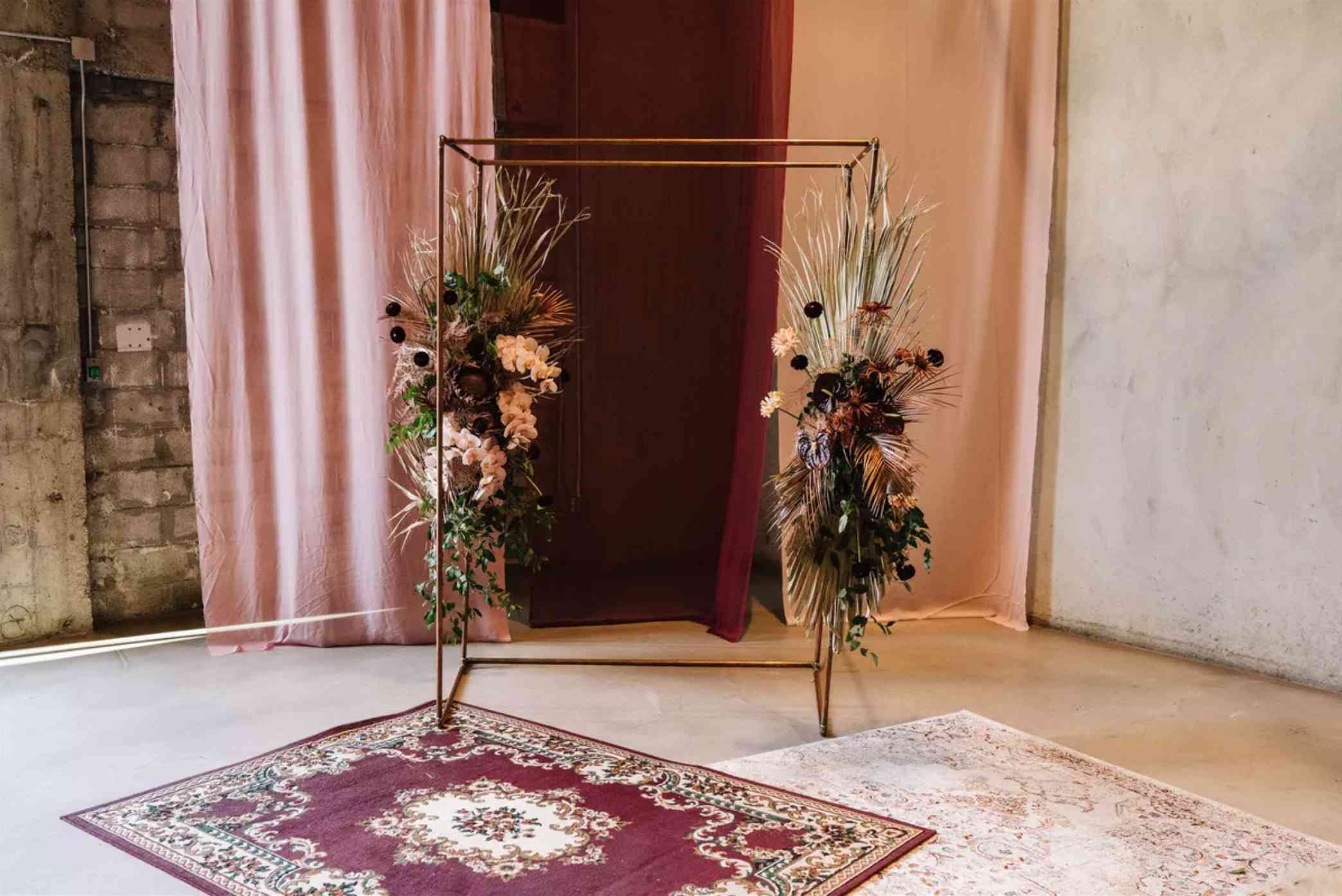 A four-post copper wedding arch accented by warm-toned seasonal flowers and dried palm leaves