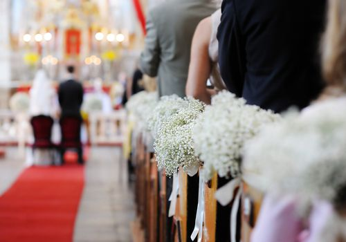 Baby's breath lining pews in church wedding, selective focus