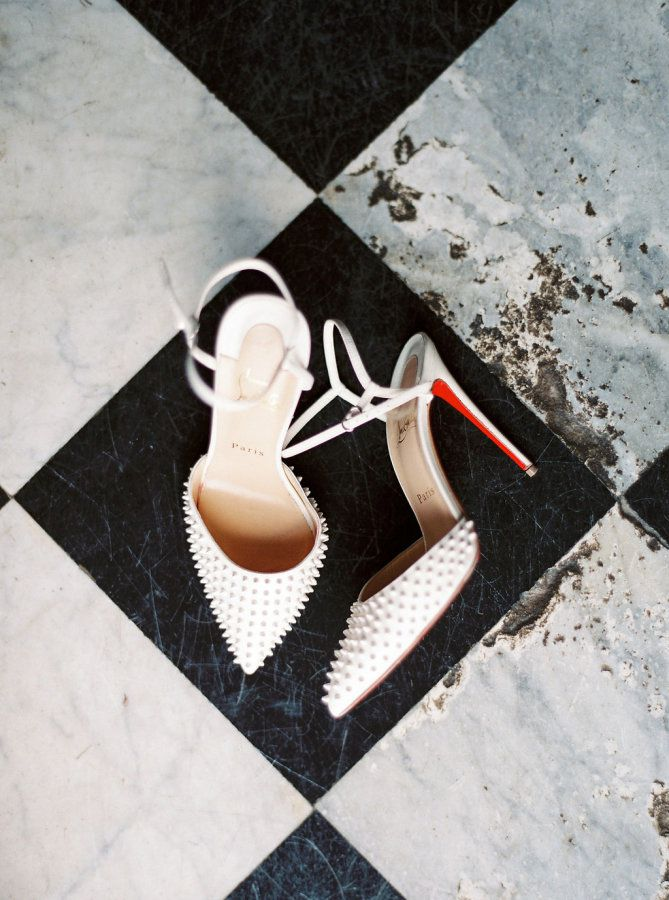 White pointed studded stilettos on a tile floor.