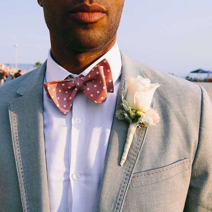 A classic boutonniere comprised of off-white roses created by Butterfly Floral and Event Design