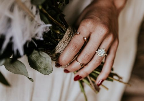 Bride's hand with cushion engagement ring and red nail polish holding bouquet