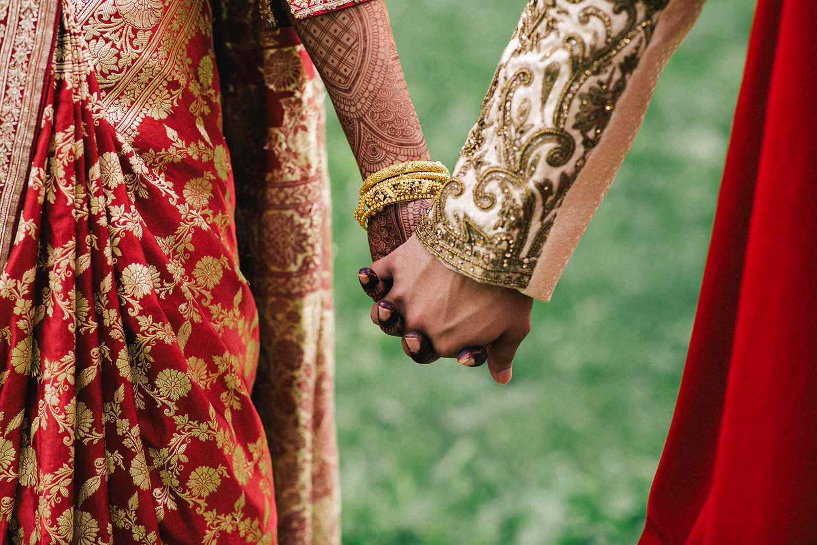 henna bride and groom holding hands