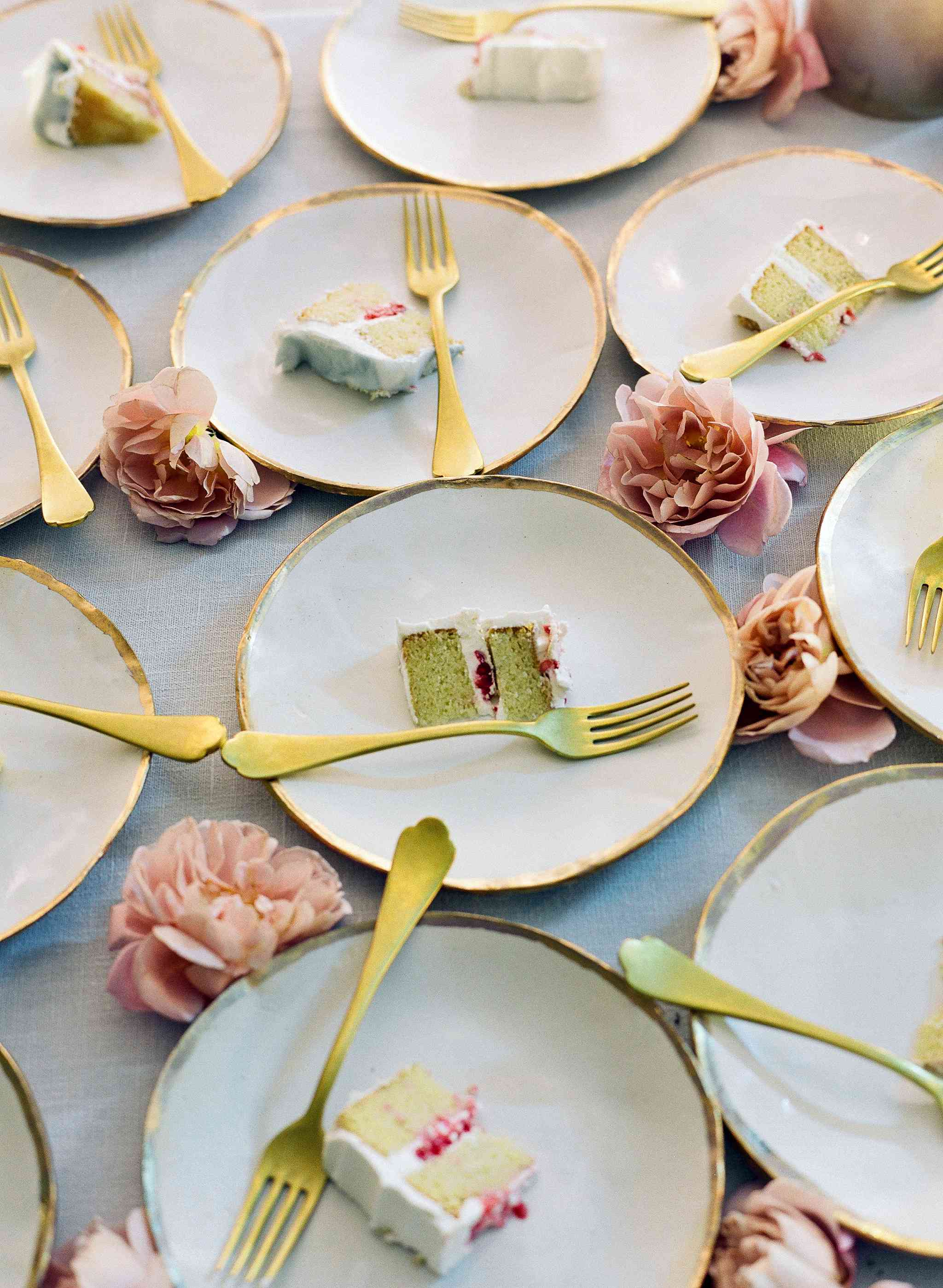 White plates with slices of cake and gold silverware