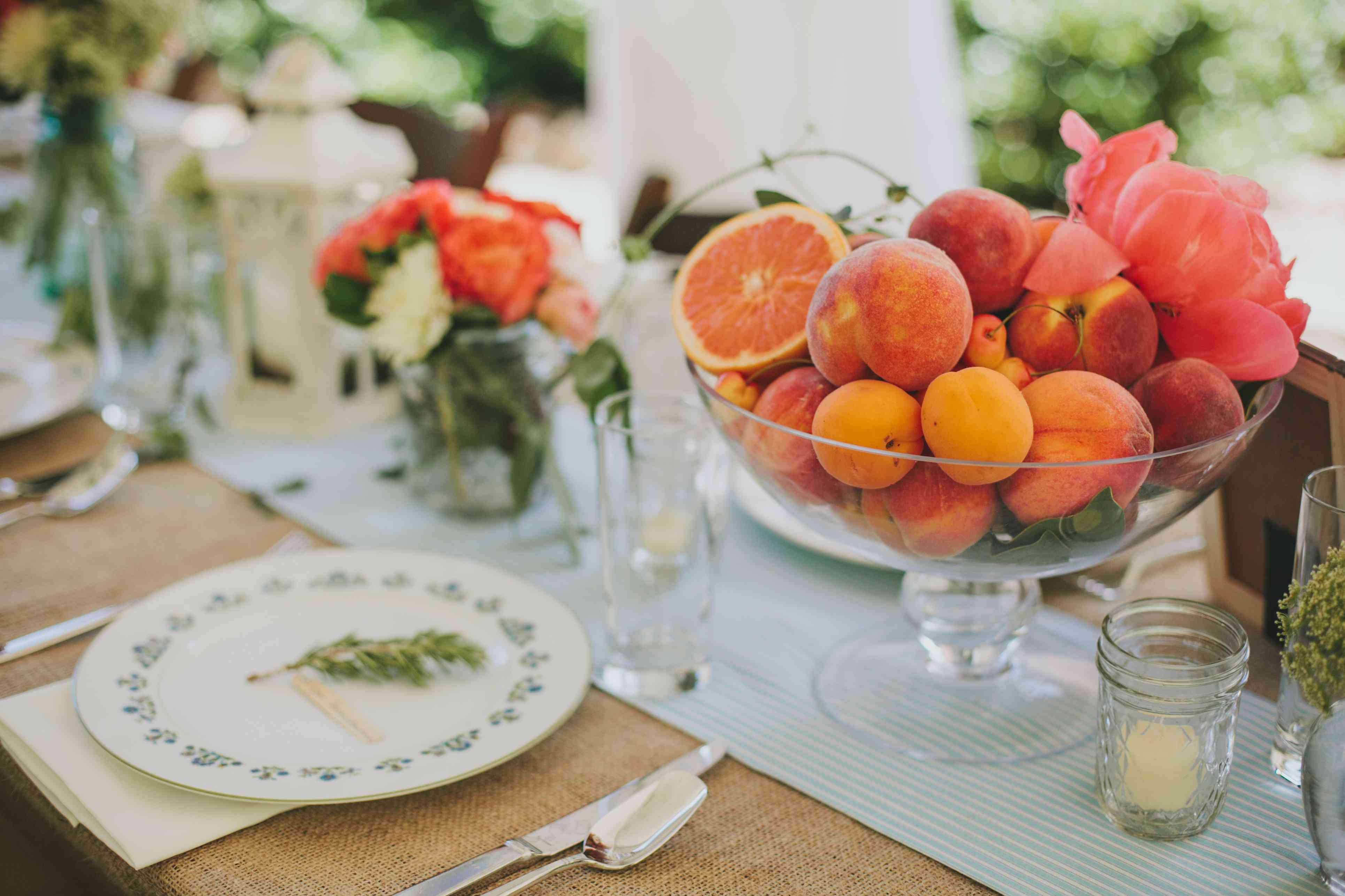 Peaches, citrus, and pink flowers as a centerpiece