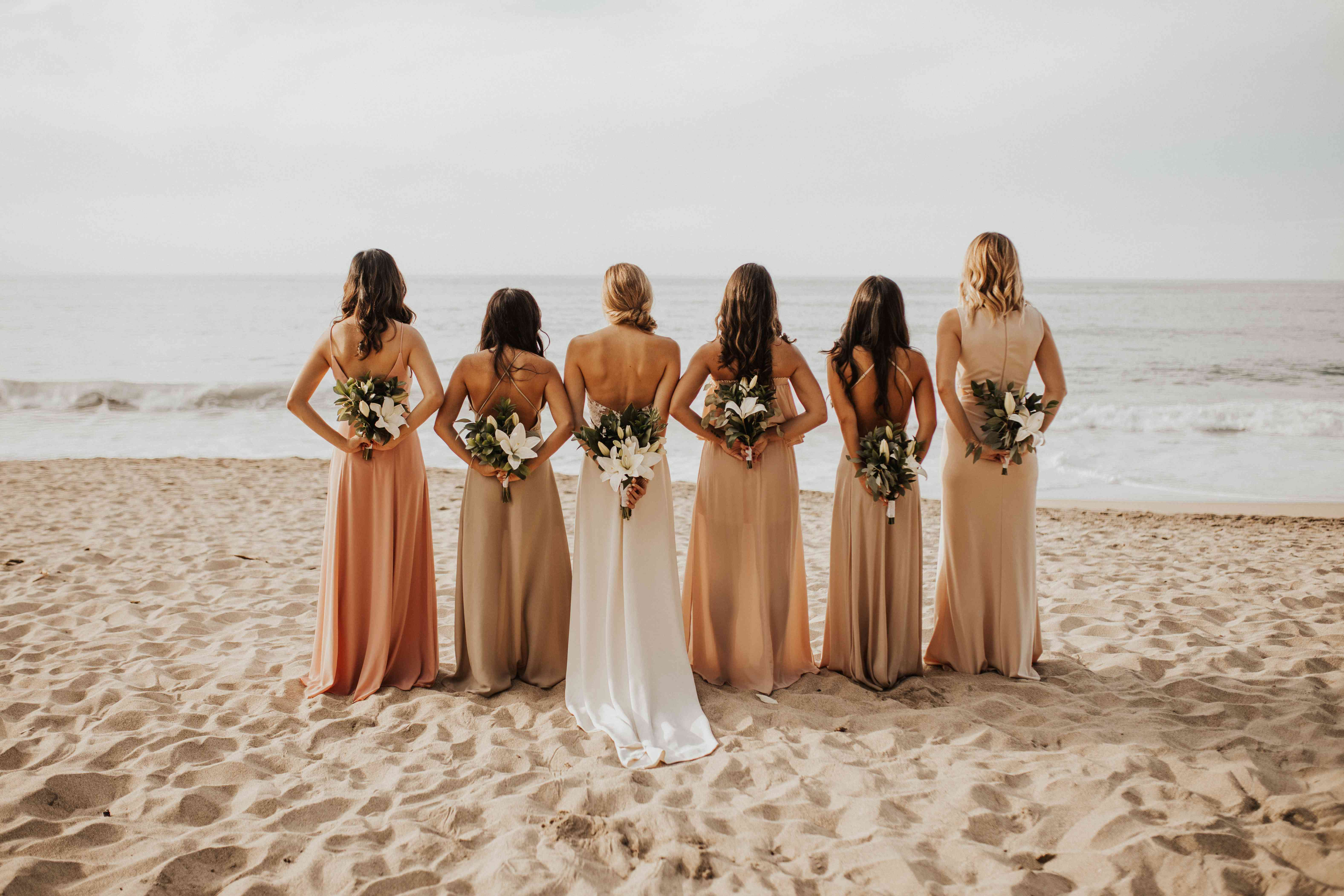 Bridesmaids and bride looking out at ocean with bouquets behind their backs