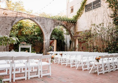 White chairs set up for wedding near brick arch