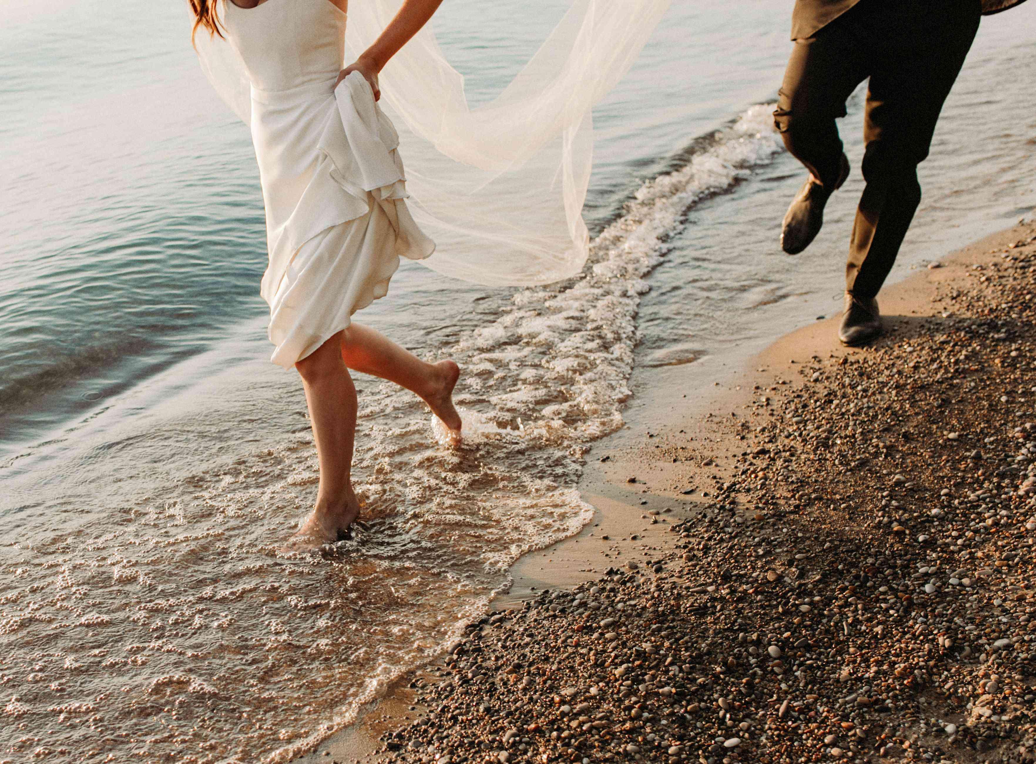 bride and groom running on beach