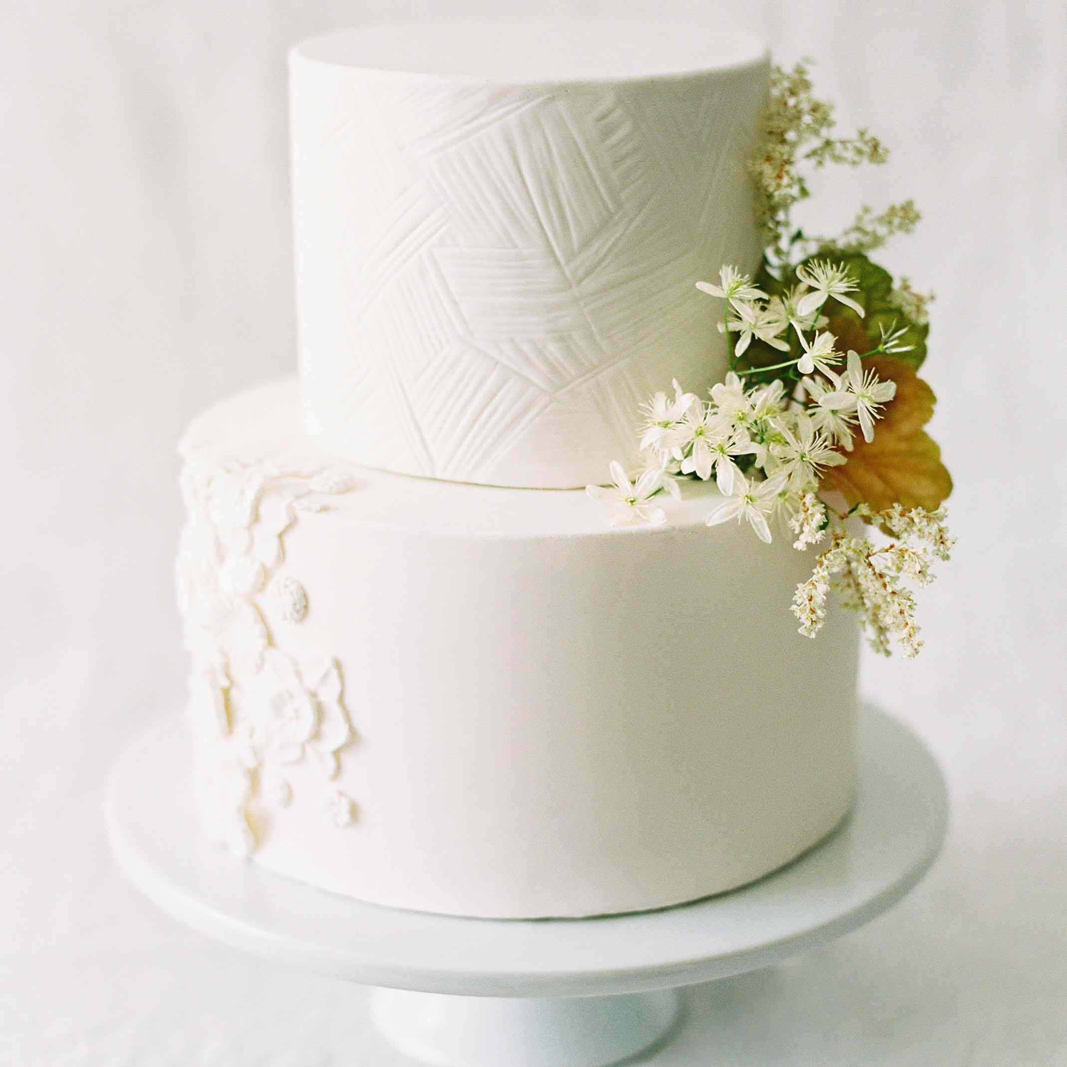 Tiered white wedding cake with floral and textural accents