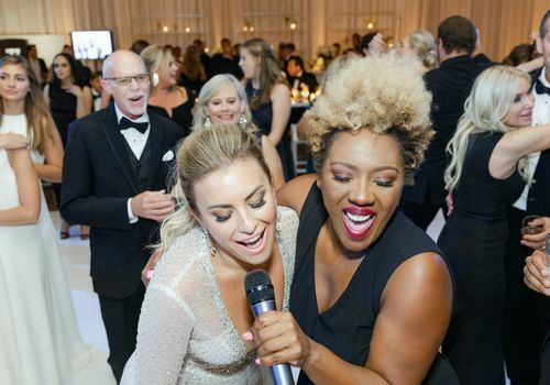 Two women singing into a microphone at a wedding reception