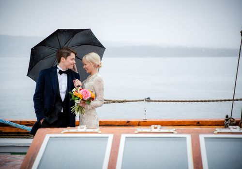 A newly-married couple standing on the deck of a sailboat in Oslo, Norway. The groom is holding an umbrella over their heads so they can stay dry.