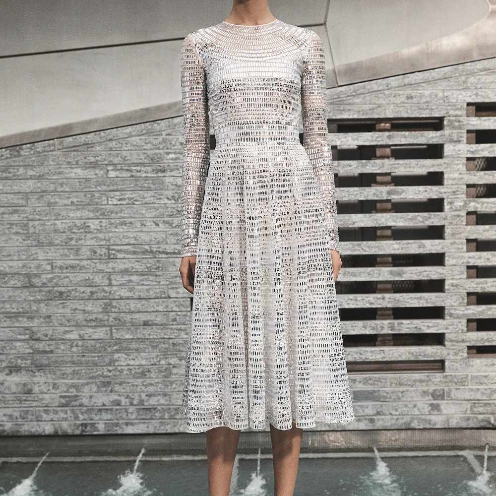 Model in long-sleeve tea length gown with silver sequins