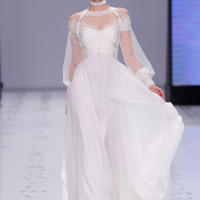 Model in a flowing plumetti and bambula dress with a lace-finished neckline and rhinestone-embroidered cuffs with a hand-sewn mini-draped bodice and sash