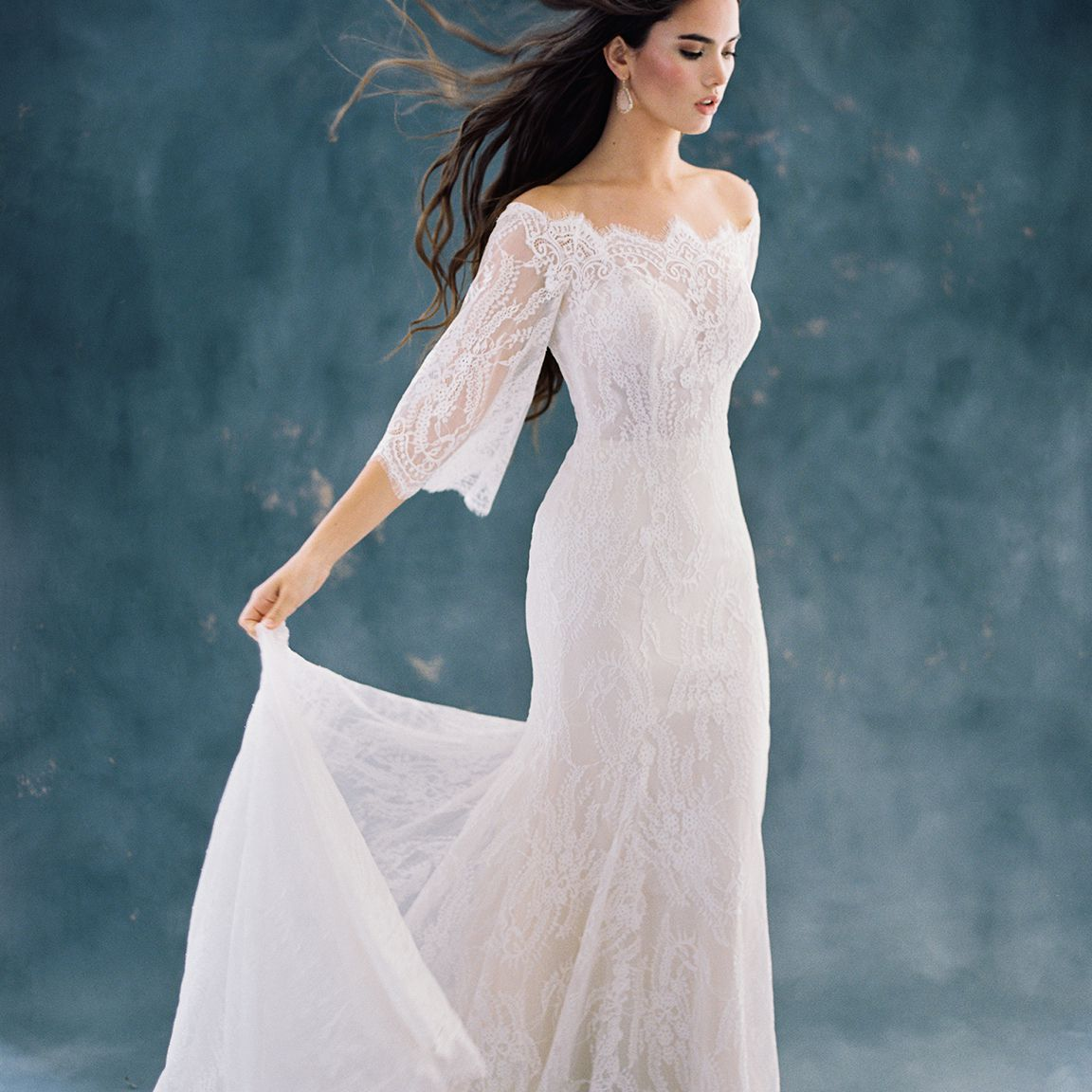 Model in lacy off-the-shoulder fit-and-flare gown with three-quarter sleeves