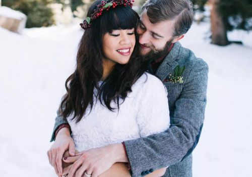 Bride wearing holly hairpiece while groom hugs her from behind in the snow outdoors