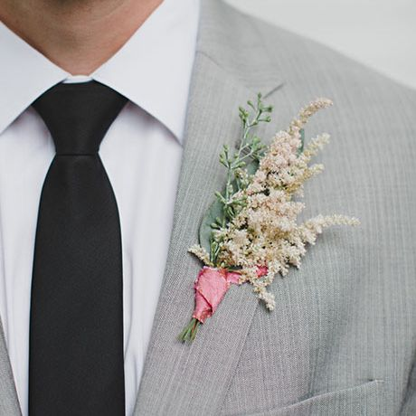 A ribbon-tied boutonniere made of astilbe and greenery, created by Mallory Joyce
