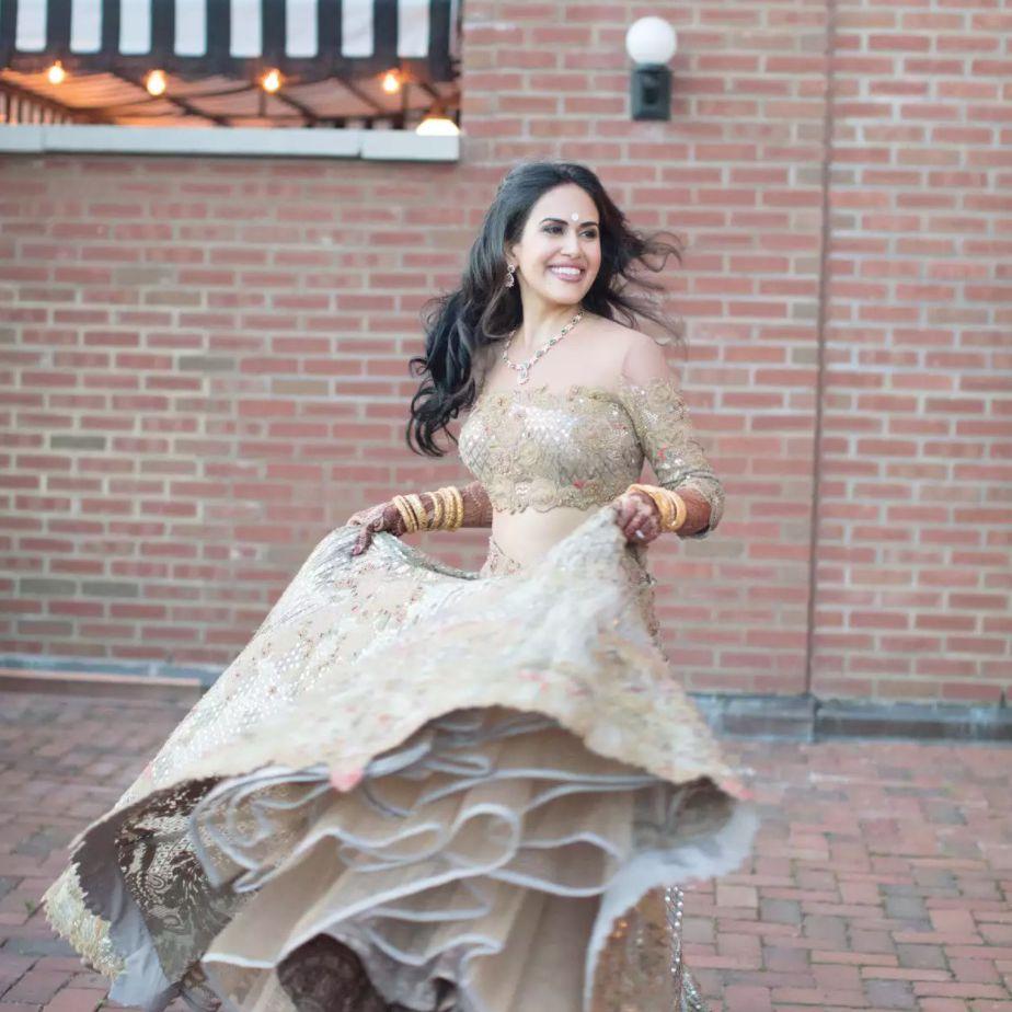 Bride twirling in glittery gold wedding lengha