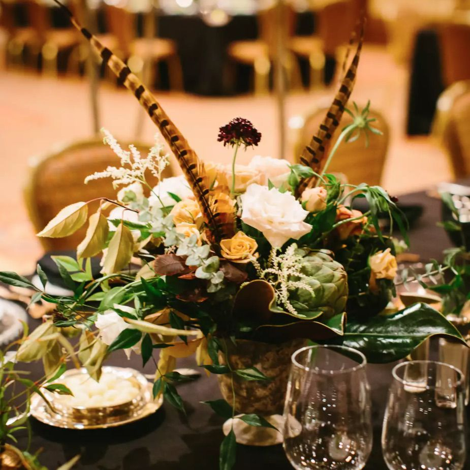 Fall centerpiece with feathers and black tablecloth