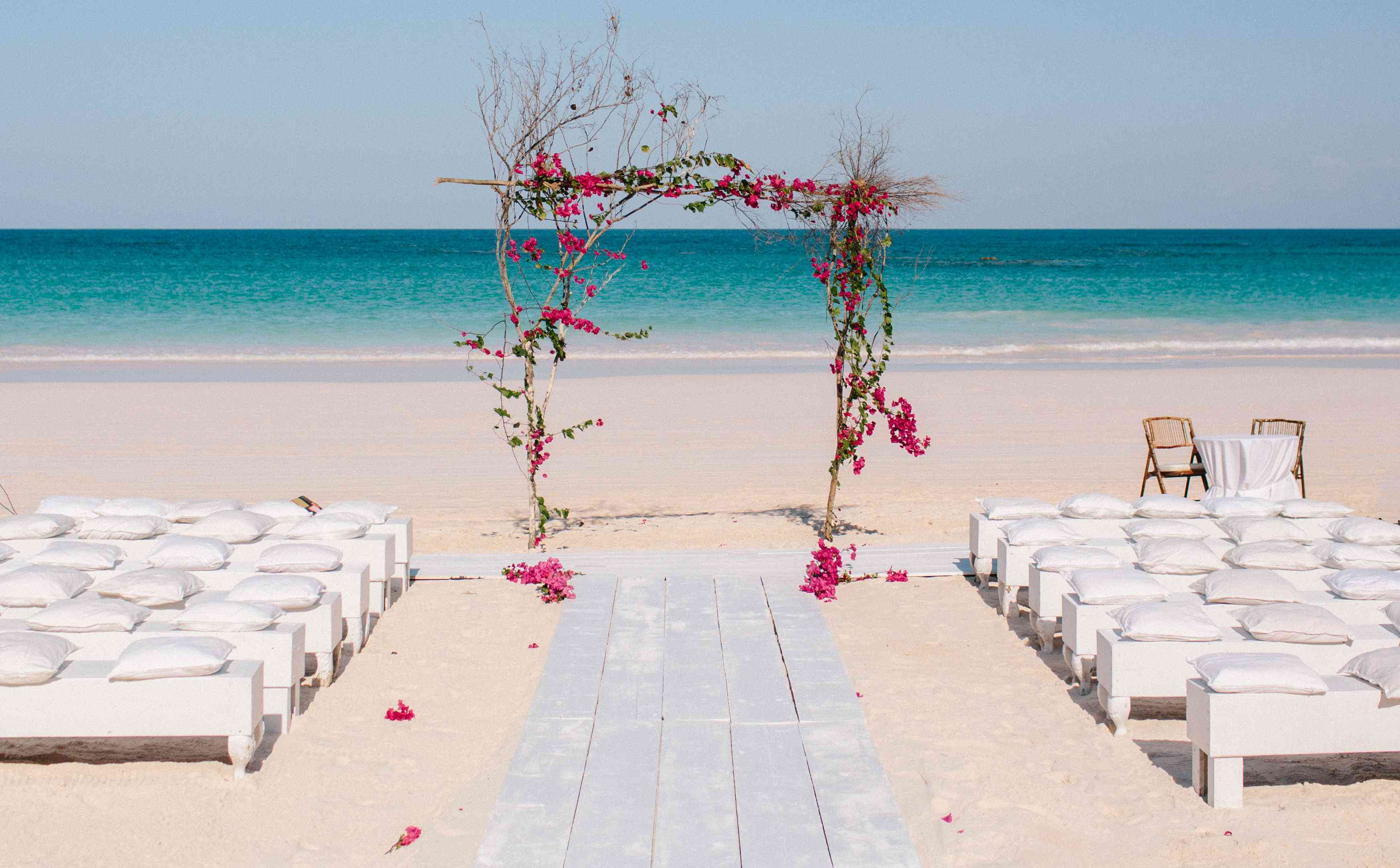 Beach wedding aisle with wooden planks to make boardwalk on sand