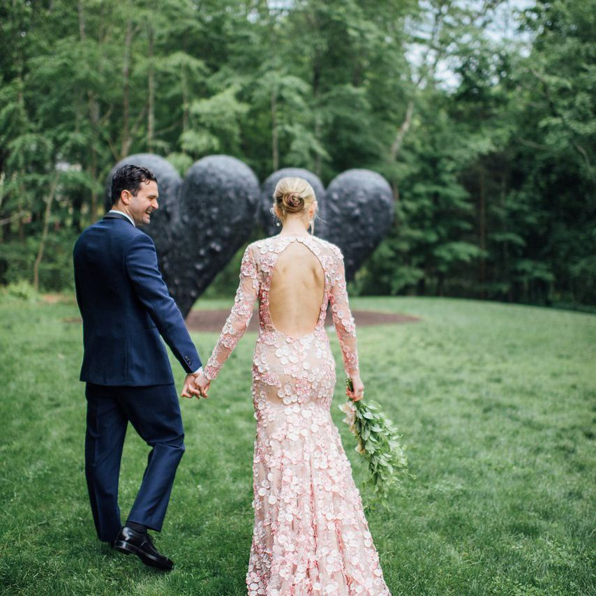 Bride and groom holding hands outside and bride in a floral pink gown