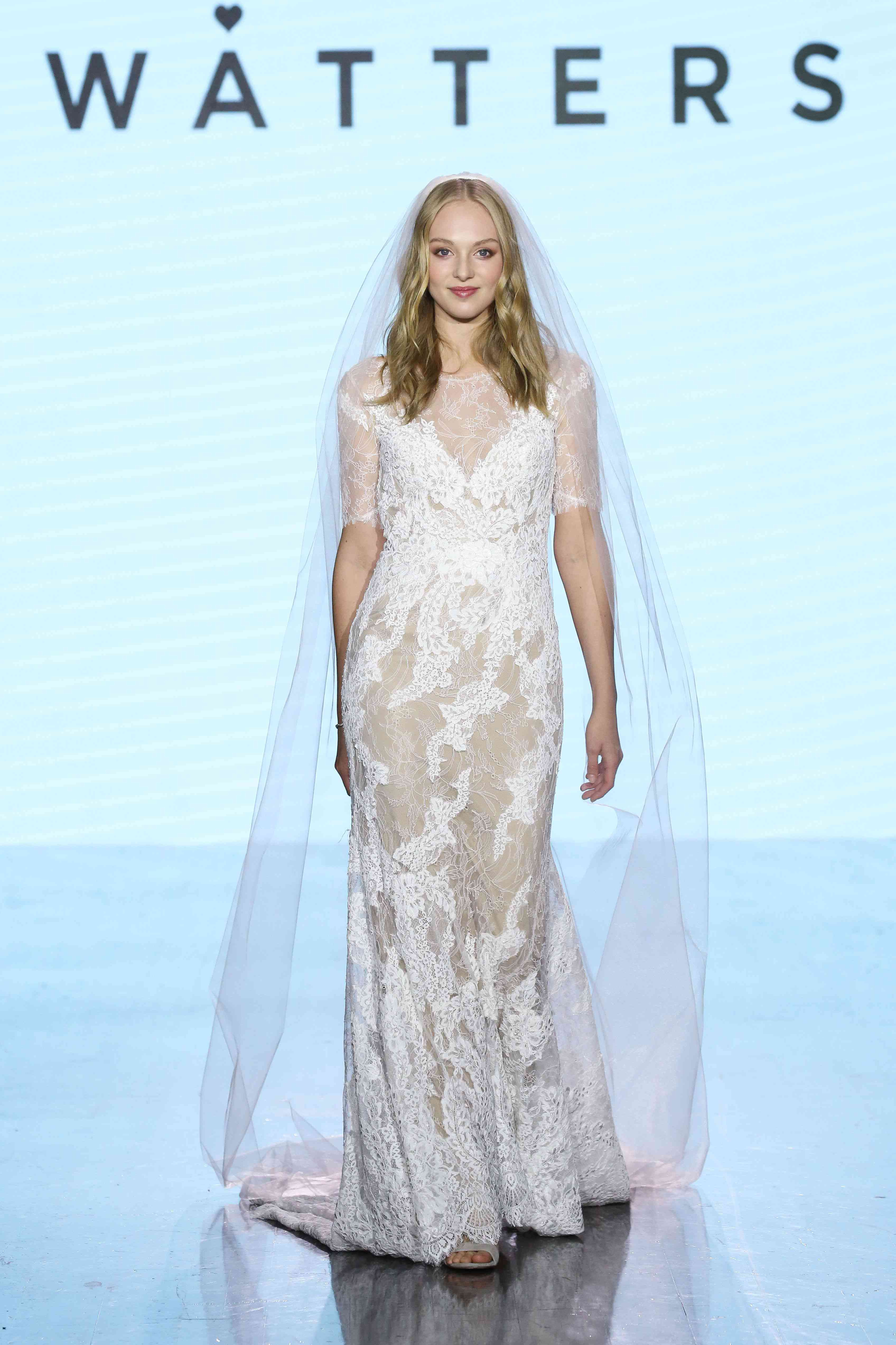 Model on runway in allover lace wedding gown with half sleeves