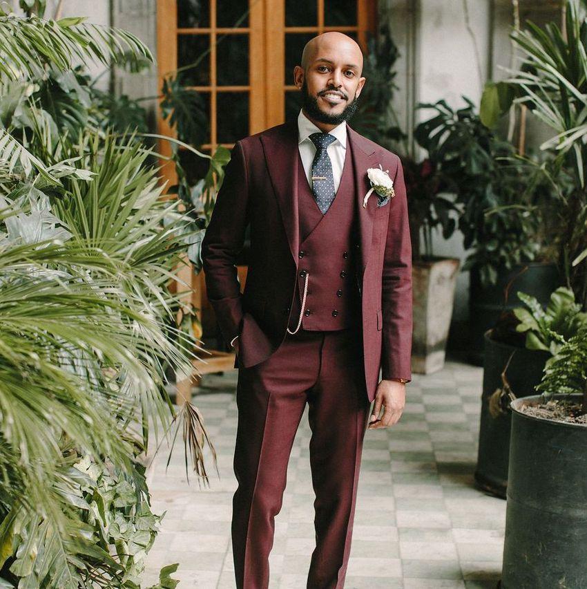 groom in burgundy suit