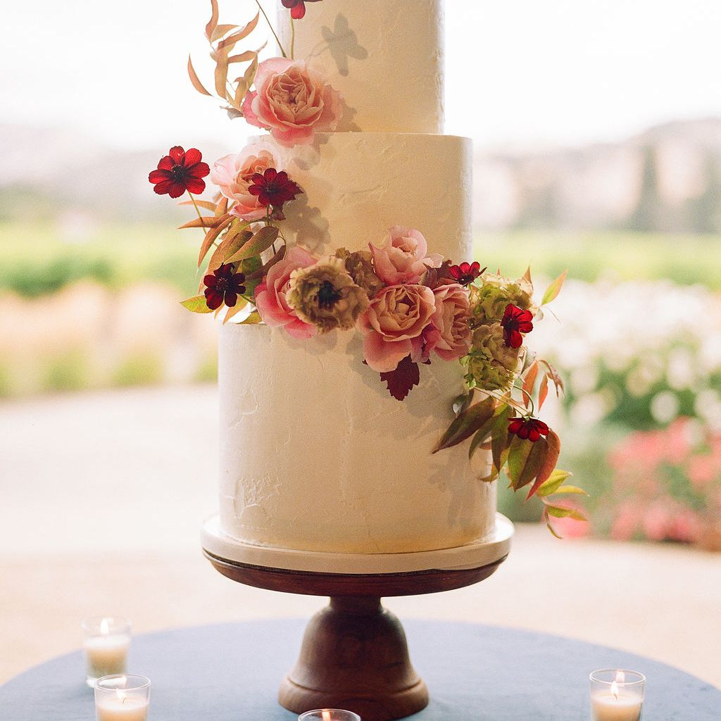 White tiered wedding cake with pink and green floral accents