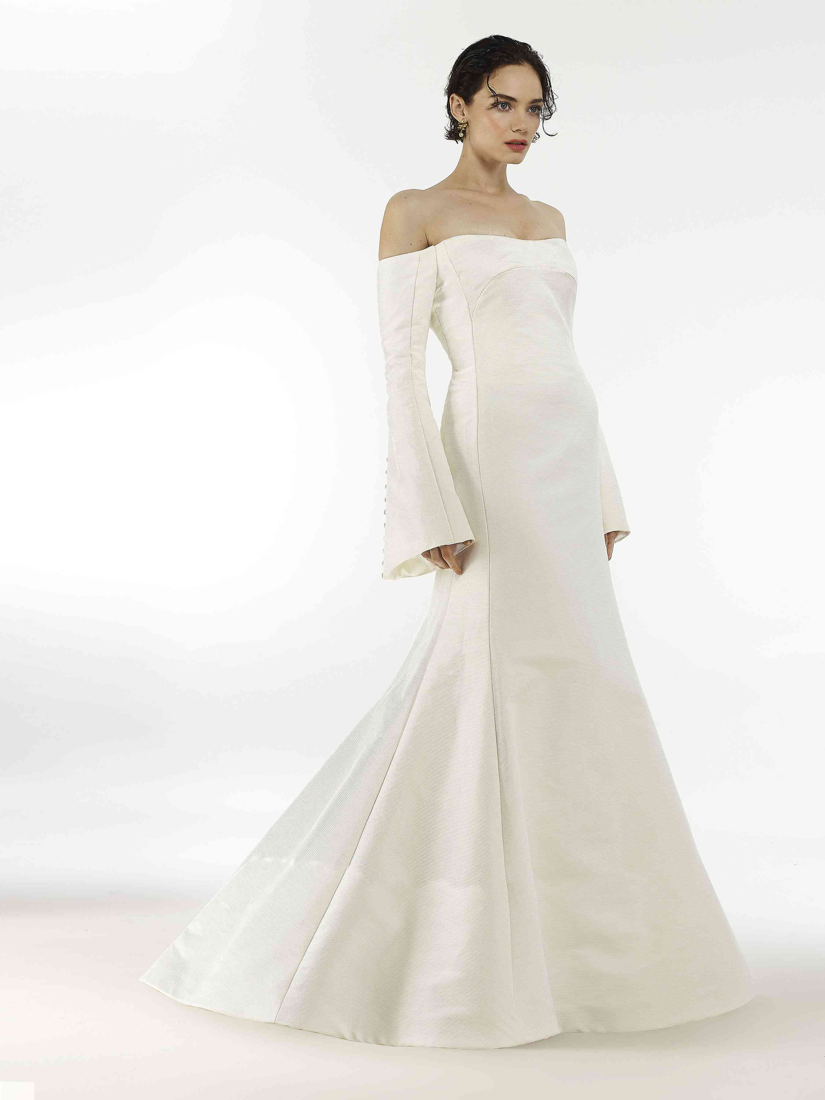 Model in long-sleeve off-the-shoulder trumpet wedding gown