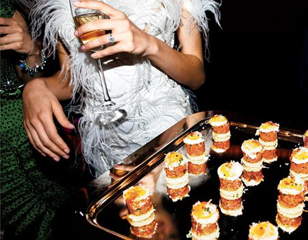 woman holding champagne with appetizers next to her