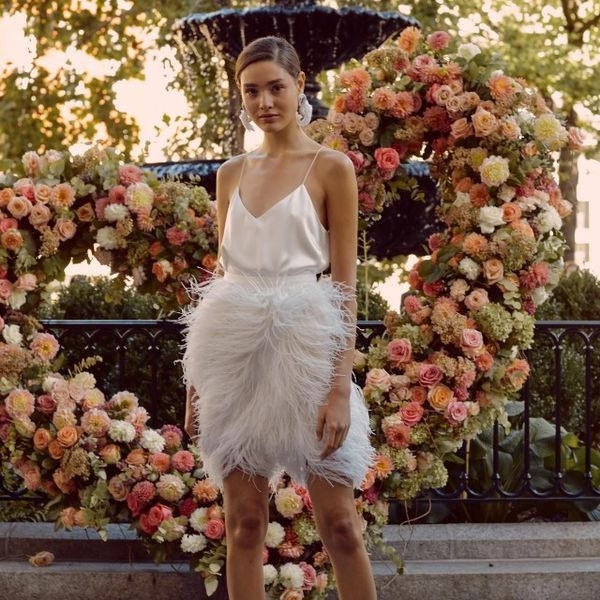 Model in short wedding dress with satin top and feathered skirt
