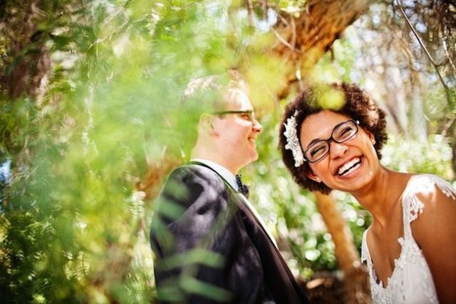 Bride wearing glasses and smiling into the camera while posing with spouse in the woods