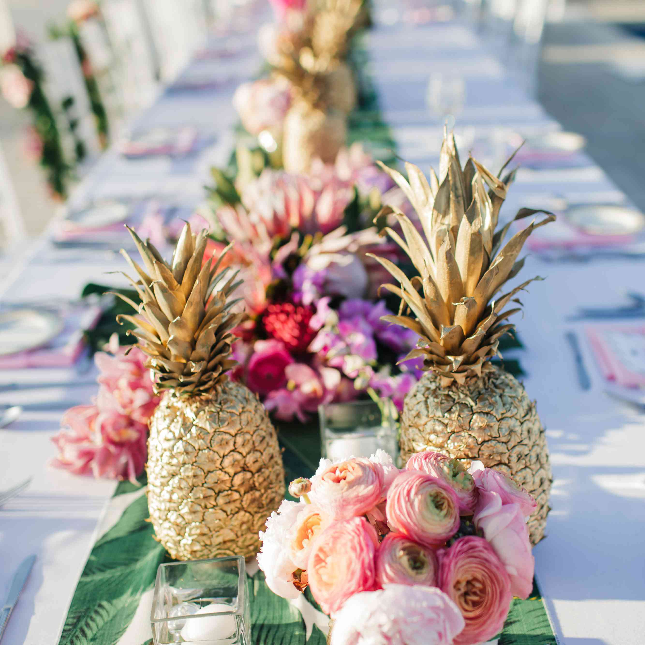 Tablescape with flowers and gold pineapples on palm print runner