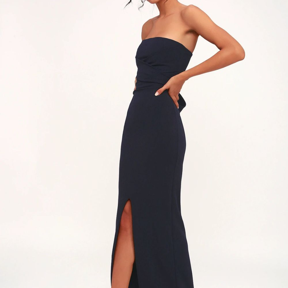 Model in a strapless navy blue gown with a side slit in the front